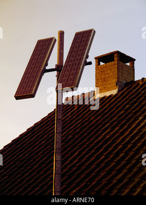 Two small solar panels mounted on a pole with a roof in the background alternative energy power - Stock Photo