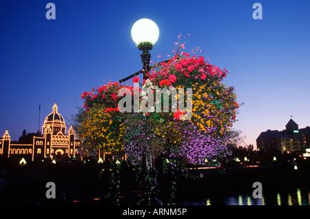 twilight with flowers on light stand and illuminated legislature, Victoria, Vancouver Island, British Columbia, Canada.
