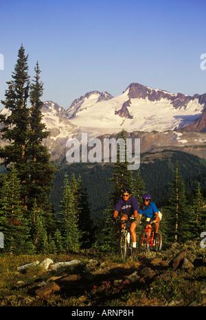 young couple ride bikes in alpine area, Whistler, British Columbia, Canada. - Stock Photo
