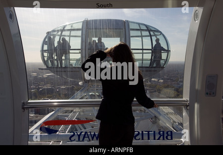 young woman enjoying the view from the window cabin of the london eye - Stock Photo