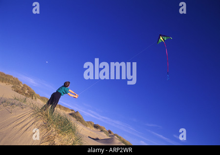 USA, Oregon Dunes National Park, 12 year old boy flies kite from dune - Stock Photo