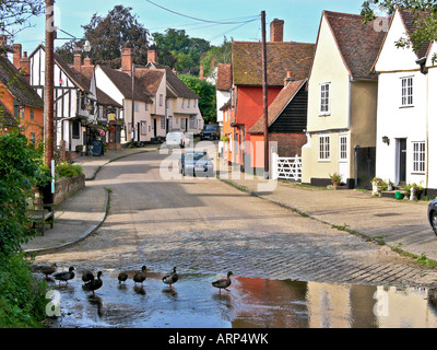 Ducks crossing the road via the ford in Kersey Suffolk England UK EU - Stock Photo
