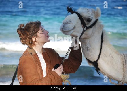 Young woman riding camel on beach, Nuweiba, Sinai Peninsula, Republic of Egypt - Stock Photo