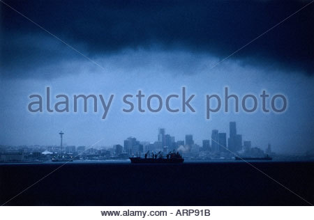 A rare blizzard blankets the Seattle Skyline in Snow, freighter lights glow on ship anchored on the Puget Sound, - Stock Photo