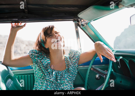 Woman in car laughing - Stock Photo