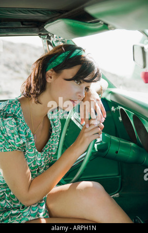 Woman in car looking pensive - Stock Photo