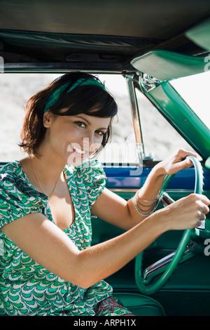 Woman in car smiling at camera - Stock Photo