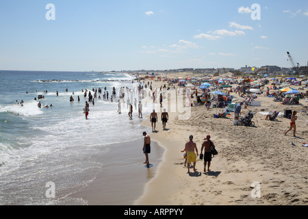 People walking along sandy surf line at the ocean edge. Mass of colorful beach umbrellas and people on sand just - Stock Photo