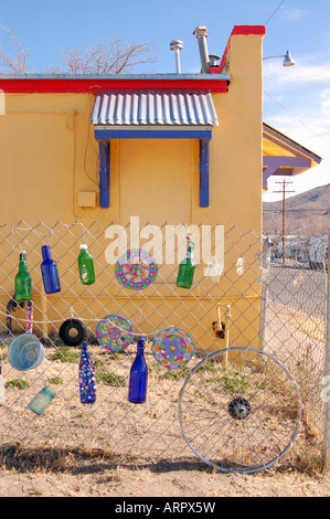 Colored bottles and other items decorate a fence in front of a New Mexico motel. - Stock Photo