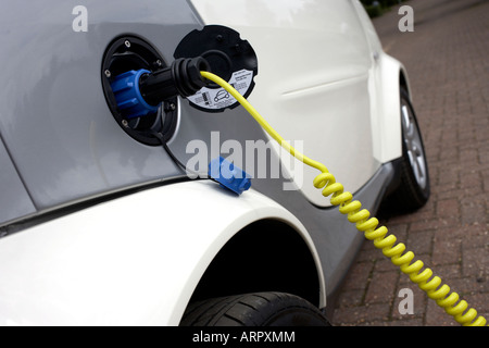 Re-charging an MHD Smart Car from mains electricity which powers its engine, an environmentally-green alternative - Stock Photo