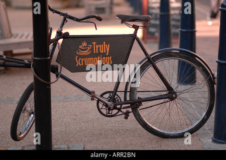 Old bicycle outside 'Truly Scrumptious' cafe. - Stock Photo