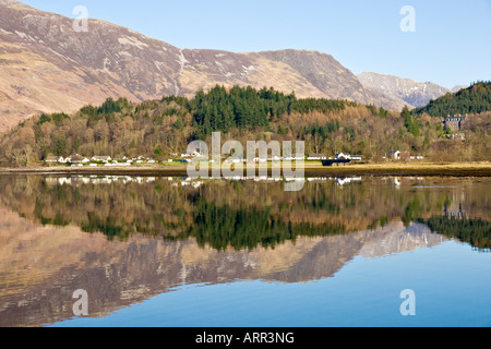 North end of Glencoe village with houses and mountains reflected in Loch leven West Highlands Scotland - Stock Photo