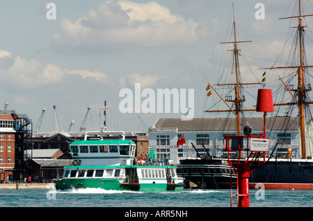 the gosport ferry making its way across portsmouth harbour with hms wario and victory in the background at the historic - Stock Photo