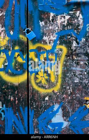 Padlock on graffiti painted doors - Stock Photo