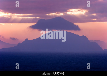 A cloud hovers over the island of Salina, part of a group of islands known as the Aeolian Islands, at sunset. - Stock Photo