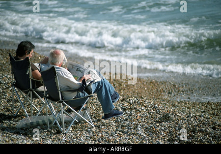An older couple sitting in deckchairs reading newspapers on a shingle beach by the sea at East Wittering in Sussex - Stock Photo