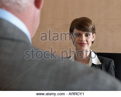 Businesswoman looking over businessman's shoulder - Stock Photo
