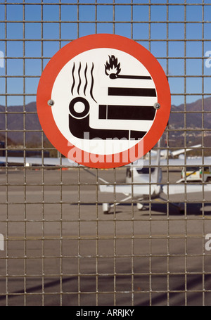 no smoking sign on the airport fencing net Switzerland - Stock Photo