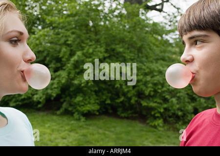 Teenage couple blowing bubble gum bubbles - Stock Photo
