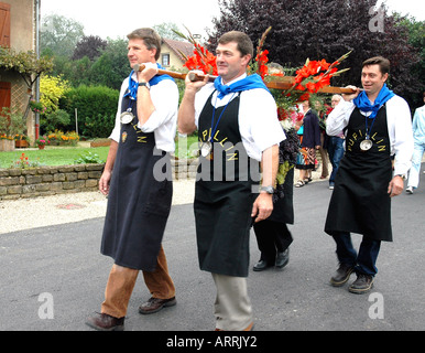 In Pupillin's annual wine festival, or biou, in France's Jura region strong men parade with the traditional huge - Stock Photo