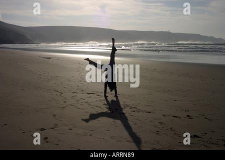 young girl cartwheeling on a beach, Pointe du Raz, Brittany, France Europe - Stock Photo