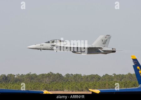 FA 18 F Super Hornet making low altitude pass with Blue Angels parked on runway in foreground - Stock Photo