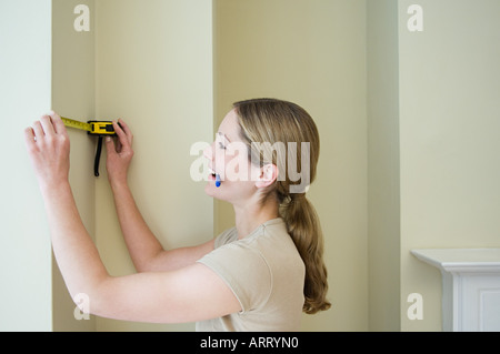 Woman measuring a wall - Stock Photo