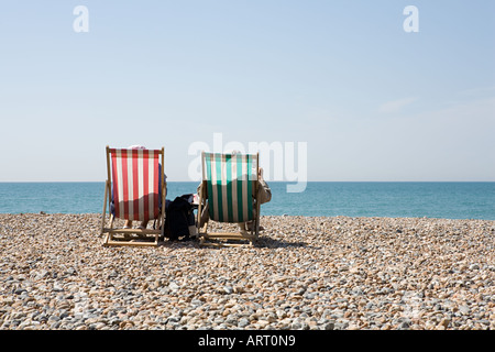 People in deckchairs at the beach - Stock Photo