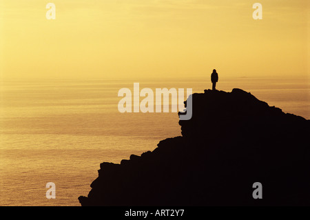 Person standing on a cliff - Stock Photo