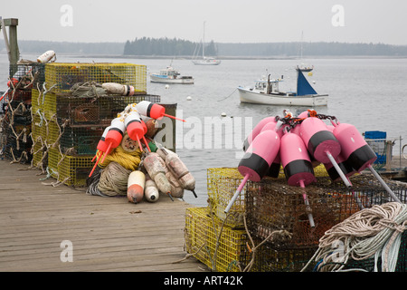 Lobster pots with brightly coloured buoys sit on the dock on a foggy day at Little Cranberry,Maine, USA. - Stock Photo