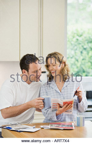 Couple looking at brochure in kitchen - Stock Photo