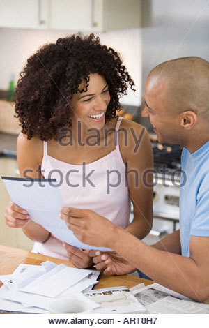 Couple reading post in kitchen - Stock Photo