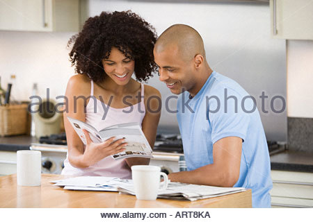Couple looking at a brochure in kitchen - Stock Photo