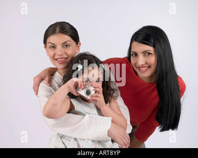 Two women and a child holding a camera - Stock Photo