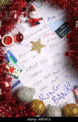 Bills, bank statement, tinsel, tree decorations and credit card statements surround a Christmas gift list. - Stock Photo
