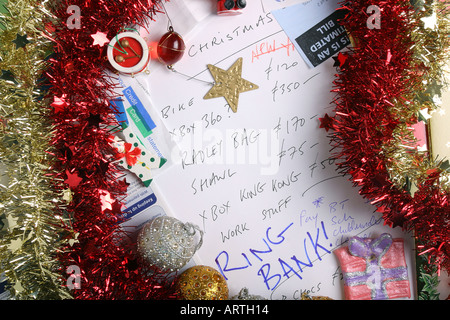 Bills, bank statement, tinsel, tree decorations and credit card statements surround a Christmas list. - Stock Photo