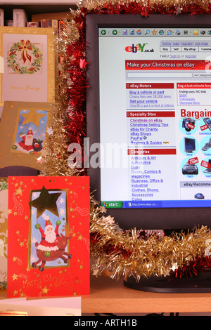 A computer screen decorated with tinsel displaying a Christmas-themed page  from the ebay web - A Computer Screen Decorated With Tinsel Displaying A Christmas