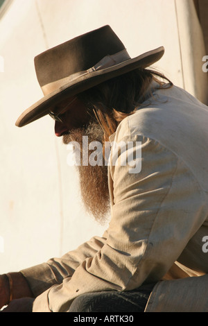 Cowboy reenactor sitting down in front of a tent at a Buffalo Bill Wild West reenactment in Wisconsin - Stock Photo