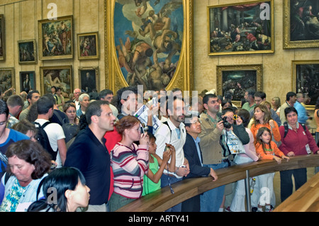 Paris France, Crowd of Tourists Looking and Photographing Leonardo Da Vinci's 'Mona Lisa' Painting in Louvre Museum - Stock Photo