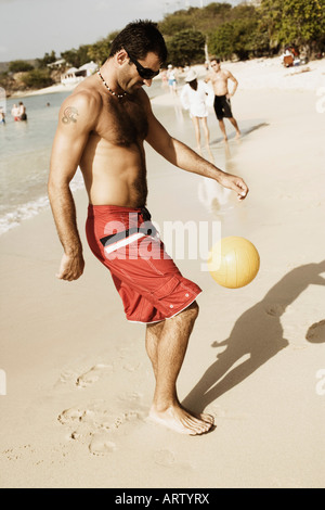 Side profile of a mid adult man playing beach volleyball on the beach - Stock Photo