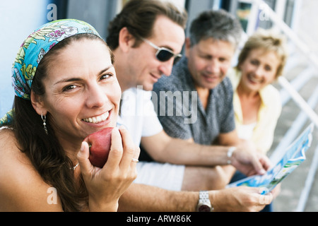 Portrait of a mid adult woman eating an apple with her friends sitting beside her - Stock Photo