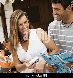 Close-up of a mid adult woman holding a digital camera and a mid adult man holding a catalog and smiling - Stock Photo