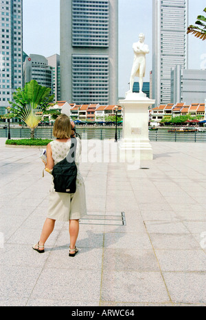 Tourist taking a photograph of the city s founder Sir Stamford Raffles statue at Raffles Landing Point in Singapore - Stock Photo
