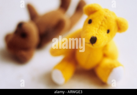 Small yellow teddy bear sitting on a white background looking at viewer with a brown ted lying alongside - Stock Photo