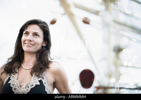 Mid adult woman on a sailing ship and smiling - Stock Photo