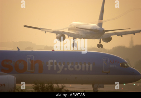 A Boeing Jet comes into land at London Gatwick Airport at dawn over a Thomson fly.com  holiday jet waiting for takeoff - Stock Photo