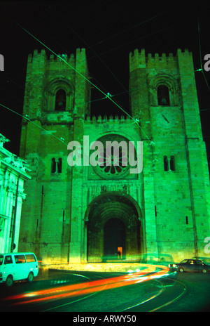 Time exposure of traffic in front of a cathedral at night in Lisbon Portugal - Stock Photo