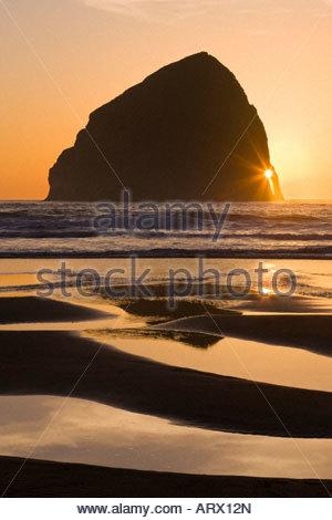 The sun shines through the arch on Haystack Rock at Cape Kiwanda, Oregon. - Stock Photo
