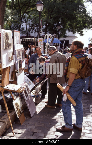 Paris Montmartre Place Du Tertre artists work on display for purchase includes man holding a baguette - Stock Photo
