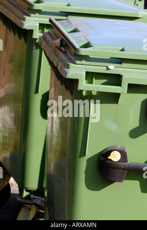 wheelie bins green coloured recyclin containers with lids lined up rows of outside of a commercial premises - Stock Photo